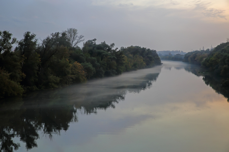 Light fog stretches over the river smooth surface of the evening dawn.