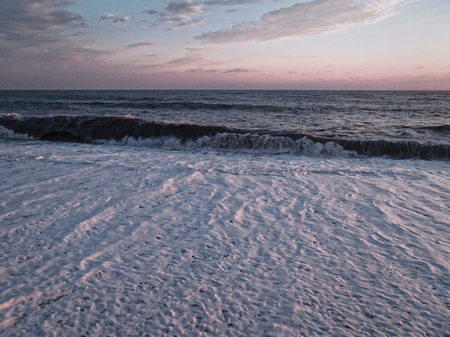 Gentle waves roll ashore.