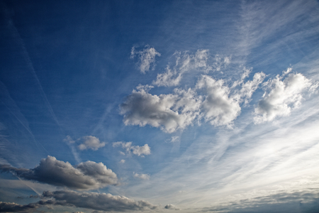 Beautiful blue sky with clouds of various shapes and colors. Фото со стока