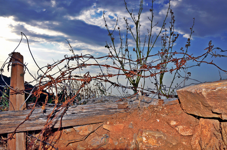 Long rusted barbed wire barrier at the end of the road under cloudy scenic sky Stock Photo