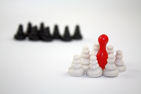 Fear from the others concept with white and dark chess pieces and one red leader.