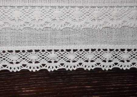 Romantic white lace textile on dark wooden desk texture