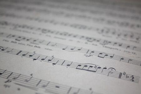 Oud muziekblad. Intreepupil wazige muzikale symbolen detailfoto.