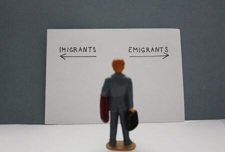 Blurry miniature man looks at emigrants and imigrants arrows. Migration concept. Archivio Fotografico