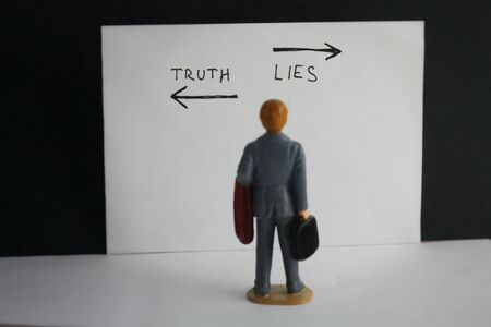 Truth and lies choice concept with miniature man decides about his way.
