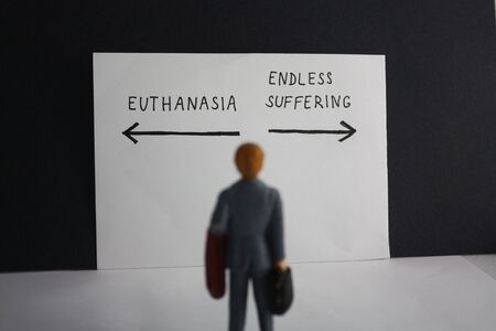 Euthanasia versus endless suffering concept with miniature man and arrows. Legalization of assisted suicice for some patients theme dillema.