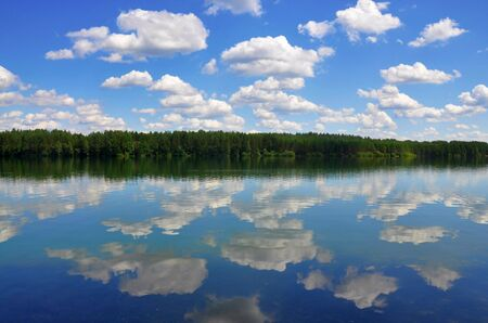 Beautiful european landscape view, forest and summer cloudy blue sky reflected in a lake like in mirror Stok Fotoğraf