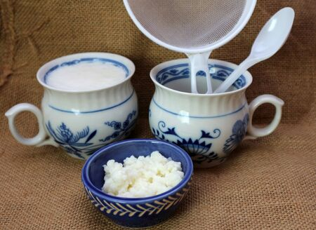Milk kefir grain and fresh homemade kefir fermented milk with plastic sieve and spoon