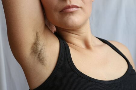 Female hairy armpit, unshaved underarms new fashion trend concept.