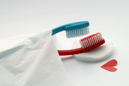Love concept of toothbrushes, red and blue totbrushes lie in bed, also missionary position metaphor.