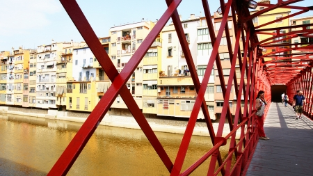 Metallic red bridge on the river O�ar with fronts to the fund in Girona, Spain