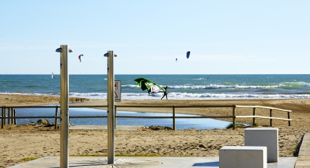 kitesurf: Castelldefels s beach, Barcelona, with puddle and showers and comets of kitesurf in the sky