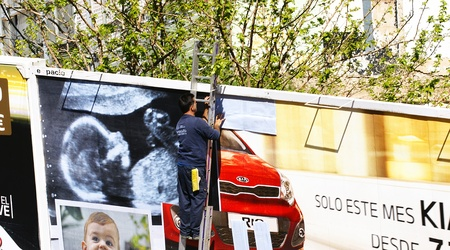 Man placing a poster into a billboard