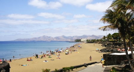 lanzarote: Beach, tourists and palm trees in Puerto del Carmen, Lanzarote, Canary Islands