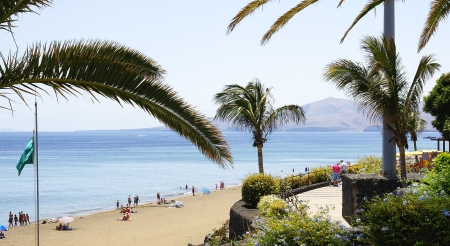 Beach, tourists and palm trees in Puerto del Carmen, Lanzarote, Canary Islands