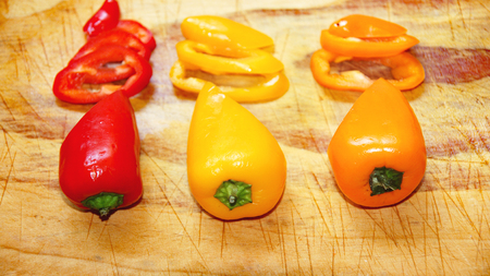 Colorful peppers on cutting board Фото со стока