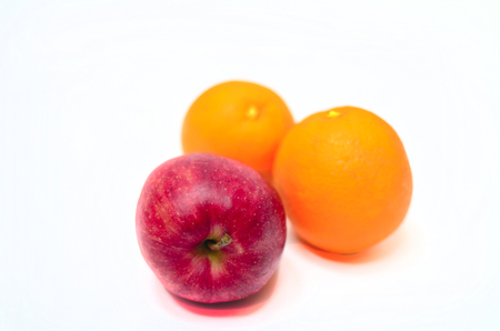 Isolated studio shot of a comparison of an apple to an orange on a white background