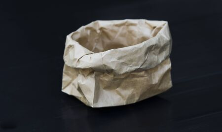 Brown paper bag on a black background. Stock Photo