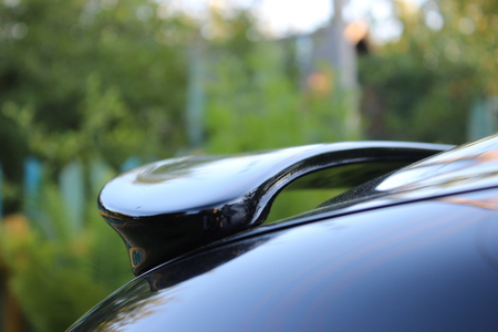 Dark spoiler car, mirroring sky, village style Stock Photo
