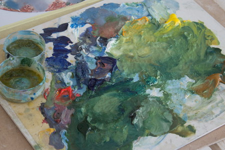 the artist's palette, mixed oil paint on Board. creative mess on the table. preparation for the drawing process.