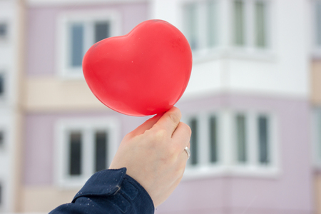 red ball-heart girl holding in her hand on background of the urban winter landscape. gift, with love on Valentines day