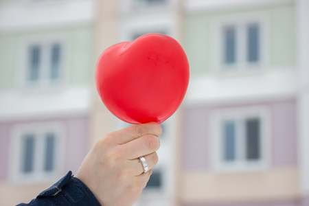 red ball-heart girl holding in her hand on background of the urban winter landscape. gift, with love on Valentine's day Фото со стока - 116546641