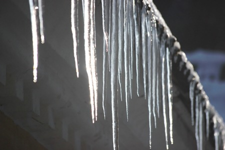 Water drops on the roof. icicles melt under influence of warm air and sun. Spring influence in the world. Modifying the pores of the years. The suns rays change aggregate state of ice to water 版權商用圖片