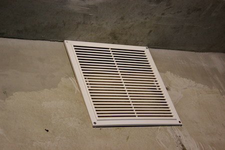 ventilation grille in apartment without finishing. concrete walls with white air grille