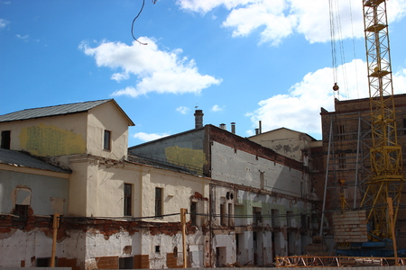 destruction of the old building, reconstruction, structural changes. construction, high-rise crane works on the site. the building is made of brick, tiles on the walls. installation, mounting, improvements
