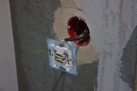 colorful wires sticking out of wall, repair the apartment, house or office. electrical wiring. light bulb and switch on the background of gray concrete wall.