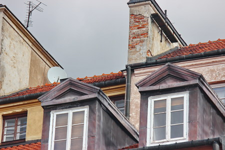 red-tiled roof with skylights in old town. protection of the house from precipitation. beautiful decor of the old building