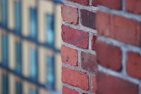 red brick wall contrasts with the modern buildings of glass, concrete and steel. wall of an old house or Church
