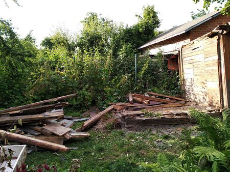 ruined house or outbuilding after hurricane. disassembled on the boards of the old building, the garbage around the house. Imagens