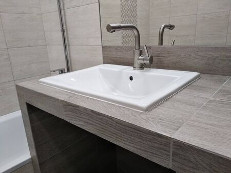 sink on table top of drywall and tiled, handmade. ease of use bathroom. niche in the countertop for a drawer with cosmetics and household chemicals Reklamní fotografie