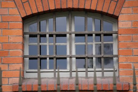 iron bars on the window of the old house, protection from thieves, illegal entry. Foto de archivo - 129172267