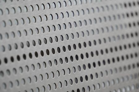 the perforated iron or metal surface, texture. Metal plate with many rounded small holes