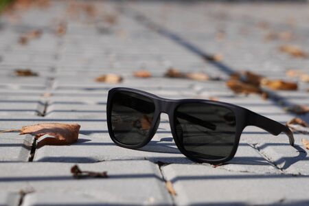 yellow dry autumn leaves have fallen and lie on the sidewalk. City street with sidewalk. Abstract symbol of autumn. close up, grey tile sidewalk. sunglasses as a symbol of summer, the change of the season
