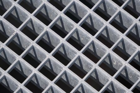 square geometry of iron plates, sturdy bars. play of light and shadow, screensaver, background. diagonal lattice background from metal. Gray tint.
