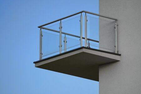 one balcony with glass railing against blue sky on Sunny day. bottom view, modern building design, Scandinavian style with white walls