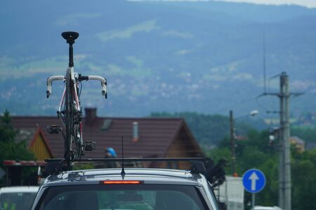 road sports bike on roof of the car against the mountains. Luggage transportation on the roof, go on a trip