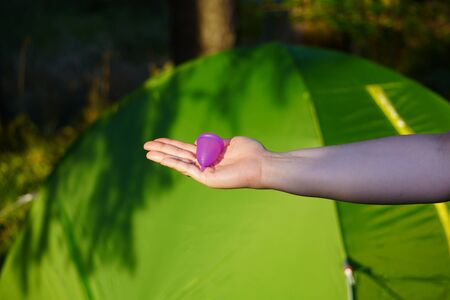 the closeup small purple menstrual Cup in girls hand on background of tent. camping, actively spend time preserving nature. zero waste, van life. Innovation product in gynecology for menstruation. 写真素材