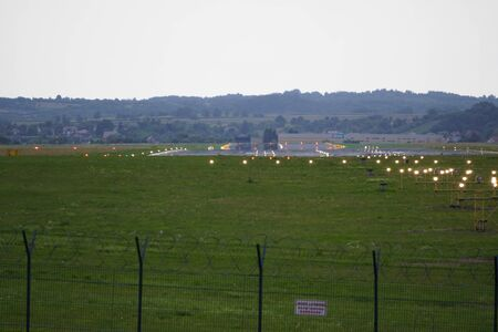 aircraft runway near the mountains. airport territory with landing lights against airport fence, closed dangerous territory.