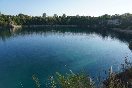 lake among rocky mountains and trees with turquoise clear water. Place is wild nature, suns and mountains reflection in clear green-blue water