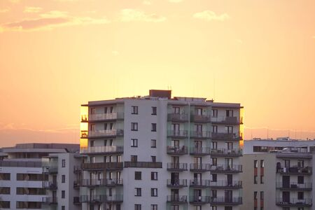 sunset light on a modern multi-storey building. the sky without clouds of different shades of red and orange. 版權商用圖片