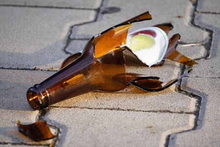 a bottle of beer, soda or drugs from dark glass is broken. Shattered beer bottle on ground in sunset light. Fragments of glass on asphalt. Texture, background, wallpaper.