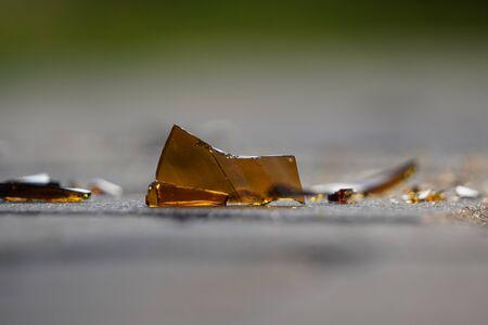abottle of beer, soda or drugs from dark glass is broken. Shattered beer bottle on ground in sunset light. Fragments of glass on asphalt. Texture, background, wallpaper. Stock Photo