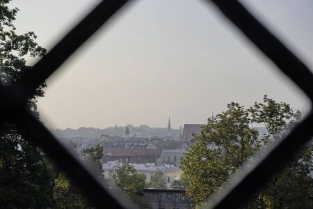 view of old town through a square hole in the fence of netting. Old building and a large number of tall trees against a light sky Stockfoto