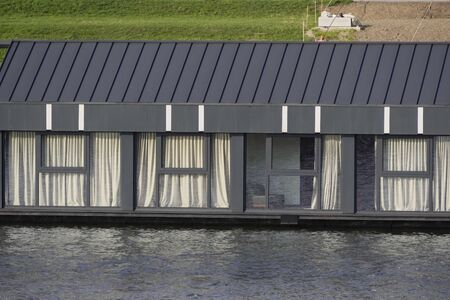 modern houseboat with large Windows and sleek design. move around country with the house on the water. van life