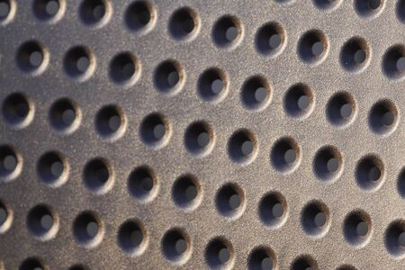 perforated material, many small holes in plastic sheet. soft sunrise or sunset light, background, texture, closeup