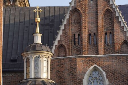 elements of Catholic Church of red brick, gold cross on the roof of the building.